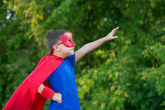 Superhero standing sideways and calling on forward. Boy dressed in cape and mask standing sideways and calling on forward stock photo