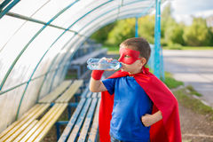 Superhero standing under canopy and drinking water from a bottle. Boy dressed in cape and mask standing under canopy and drinking water from a bottle stock images
