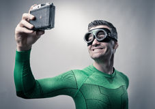 Superhero taking a selfie with a vintage camera Royalty Free Stock Photo