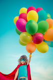 Superhero with toy balloons in spring field Stock Images