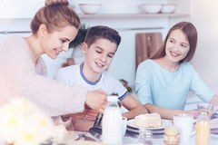 Loving mother taking care of children during family breakfast time. She is a superhero for us. Tender cheerful women sitting next to her kids and pouring Royalty Free Stock Photo