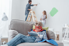 Superhero using a tablet and home makeover Stock Photo