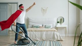 Superhero wearing red cape and mask holding vacuum cleaner in bedroom. Superhero wearing red cape and mask is holding vacuum cleaner in bedroom ready to clean stock video footage