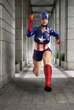 Superhero Woman, Crime Fighter, Justice. Truth, justice, and the American way! A superhero woman who looks like Captain America is running through the city Stock Images