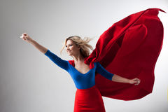 Superhero Woman. Young and beautiful blonde in image of superheroine in red Cape growing. Superhero Woman. Young and beautiful blonde in the image of a stock photo