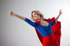 Superhero Woman. Young and beautiful blonde in image of superheroine in red Cape growing Stock Photo