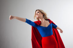 Superhero Woman. Young and beautiful blonde in image of superheroine in red Cape growing Stock Photos