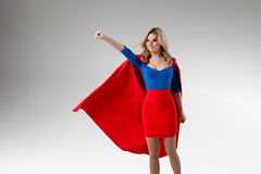 Superhero Woman. Young and beautiful blonde in image of superheroine in red Cape growing Royalty Free Stock Photography