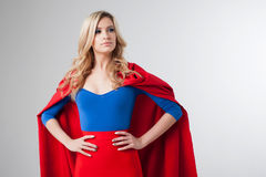 Superhero Woman. Young and beautiful blonde in image of superheroine in red Cape growing Royalty Free Stock Photo