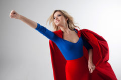 Superhero Woman. Young and beautiful blonde in image of superheroine in red Cape growing Royalty Free Stock Images