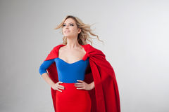 Superhero Woman. Young and beautiful blonde in image of superheroine in red Cape growing Stock Photography