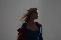 Superhero Woman. Young and beautiful blonde in image of superheroine in red Cape growing Royalty Free Stock Image