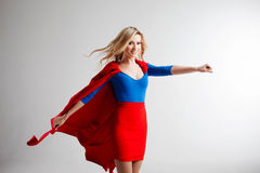 Superhero Woman. Young and beautiful blonde in image of superheroine in red Cape growing. Superhero Woman. Young and beautiful blonde in the image of a stock photos
