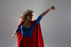 Superhero Woman. Young and beautiful blonde in image of superheroine in red Cape growing. Superhero Woman. Young and beautiful blonde in the image of a royalty free stock photo