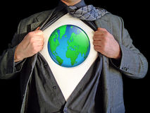Superhero world map. A business man isolated against a black background tearing open his shirt to reveal a world map on a t shirt royalty free stock photo