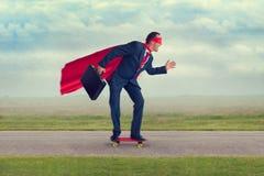 Superheroaffärsman som rider en skateboard arkivbild
