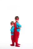 Superheroen för två pojke med en full längd för maskering och för kappa ser kameran royaltyfri foto