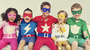 Superheroes Kids Friends Playing Togetherness Fun Concept. Kids superhero costume sitting in row Royalty Free Stock Images
