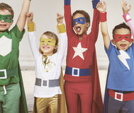 Superheroes Kids Teamwork Aspiration Elementary Concept. Four kids in superhero costume raise their hands and enjoy happy time Royalty Free Stock Image