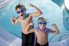 Superheroes show their muscles by swimming pool Stock Photography