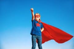 Superheroheld van het concepten gelukkige kind in rode mantel in aard stock afbeeldingen