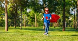 Superheroheld van het concepten gelukkige kind in rode mantel in aard royalty-vrije stock foto's