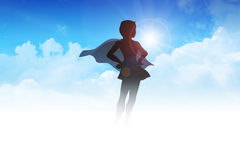 Superheroine. Silhouette of a female figure with superhero suit on clouds Stock Image