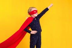 Superheroliten flicka i en röd regnrock och en maskering Royaltyfria Foton