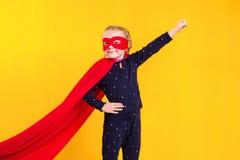 Superheroliten flicka i en röd regnrock och en maskering Arkivfoto