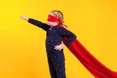 Superheroliten flicka i en röd regnrock och en maskering Royaltyfri Fotografi