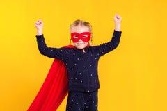 Superheroliten flicka i en röd regnrock och en maskering Arkivbild