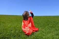 Superherolitet barnpunkter in mot dramatisk blå himmel arkivbild
