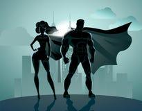 Superheropaar: Mannetje en wijfje superheroes, stellend vooraan o Stock Afbeelding
