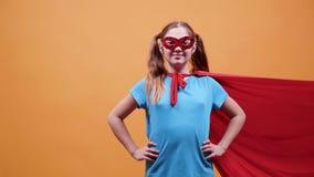 Superheroung flicka med en röd kappa och en maskering på hennes ögon stock video