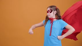 Superheroung flicka som stiger hennes hand till himlen som förbereder sig att ta av arkivfilmer