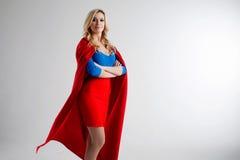 Superherovrouw Jong en mooi blonde in beeld van superheroine in het rode Kaap groeien royalty-vrije stock foto
