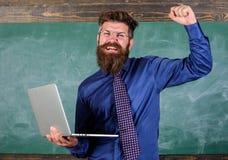 Superi la prova online Concetto di istruzione a distanza L'uomo barbuto dell'insegnante con il computer portatile moderno ha pass fotografie stock libere da diritti