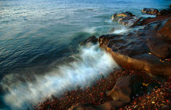 Superior Wave. Wave crashing on shore in early morning light stock photography