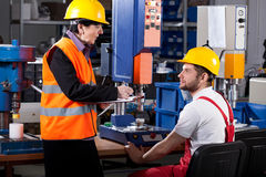 Superior and worker in warehouse. Elder female superior is instructing young male worker royalty free stock images