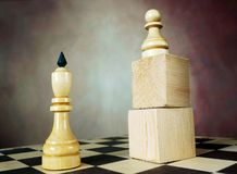 Chess pawn has an advantage over chess king because he stands on a wooden stand. Superiority. Concept with chess pieces. Chess pawn has an advantage over chess Royalty Free Stock Photos