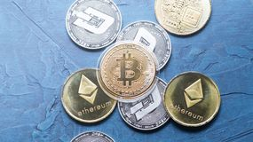 Superiority of the Crypto-currency: A bitcoin coin is among the various coins on a blue background. Superiority of the Crypto-currency: A large gilt bitcoin stock photos