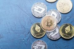 Superiority of the Crypto-currency: A bitcoin coin is among the various coins of the world on a gray background. Superiority of the Crypto-currency: A large stock images