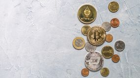 Superiority of the Crypto-currency: A bitcoin coin is among the various coins of the world on a gray background. Superiority of the Crypto-currency: A large stock photography