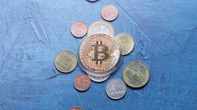Superiority of the Crypto-currency: A bitcoin coin is among the various coins of the world on a gray background. Superiority of the Crypto-currency: A large royalty free stock photography