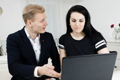 Superiors works with subordinate. Blond man explains black haired woman royalty free stock photography