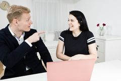 Superiors works with subordinate. Blond man points finger at black haired woman royalty free stock images