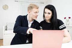 Superiors works with subordinate. Blond man working with black haired woman royalty free stock photo