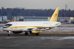 Superjet 100 RA-89004 Tsentr-Yug Sukhoi in der goldenen Livree, die an internationalem Flughafen Sheremetyevo mit einem Taxi fähr Lizenzfreie Stockbilder