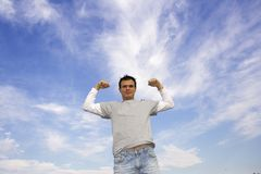 Superman. Man flexing muscles with the blue sky background stock photography
