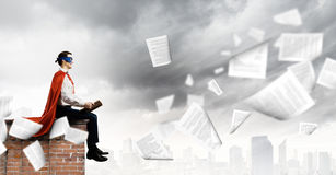 Superman with book. Superman in cape and mask sitting on top of building and reading book Royalty Free Stock Photo